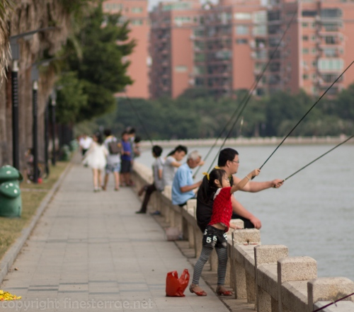 A girl and her father fishing on Xiamen's Yundang Inner Lake.