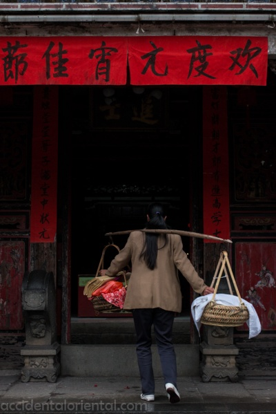 A woman delivers offerings for her ancestors to the Taxia village Taoist temple.